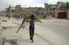 Un hombre lleva un tiburón por las calles de Mogadiscio, Somalia, el 23 de septiembre de 2010. | World Press Photo - Awareness's blog