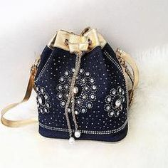 Bucket bag design complete with rivets and rhinestones, different style detachable strap that gives you more options, chain closure with metail eyelit, spacious compartment with interior pockets. Craf