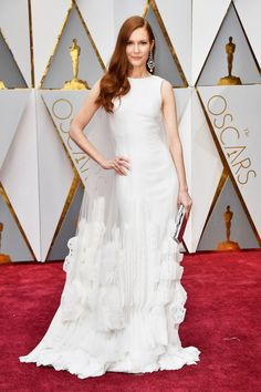 2017 Oscars: Darby Stanchfield is wearing a white Georges Chakra Couture gown with a sheer cape with tulle. Beautiful dress! I like the cape detail. Her earrings are stunning! The earrings pop really well with the white gown!