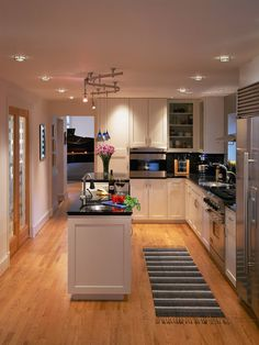 Small Kitchen Designs with Amazing Furniture Arrangements: Recessed Lighting And Pendant Lighting With White Shaker Kitchen Cabinets Also Black Countertops And Kitchen Island With Sink For Small Kitchen Designs Plus Oak Flooring Square Kitchen Layout, L Shape Kitchen Layout, Small Kitchen Layouts, Best Kitchen Designs, Modern Kitchen Design, Kitchen Photos, Long Narrow Kitchen, Kitchen Island With Sink, New Kitchen