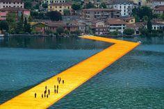 """C'est au lac d'Iseo dans les préalpes italiennes que vous pouvez découvrir et expérimenter, jusqu'au 3 juillet, cette incroyable passerelle flottante intitulée """"The Floating Piers"""" par l'artiste Christo.  Cette passerelle flottante mesure plus de 3 km et relie deux petites îles du lac au continent. Recouverte de 100.000 m2 de tissu jaune chatoyant, elle est portée par un système flottant de quai modulaire composé de 220 000 cubes en polyéthylène haute densité soufflé. Les visiteurs…"""