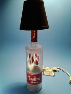 Three Olives® Raspberry Liquor Bottle Table Lamp W/ Black Shade This is a Quality Handmade Liquor Bottle Table Lamp This liquor bottle lamp is a unique way to light your home, whether on a table, b. Light Table, A Table, Table Lamp, Bottle Lamps, Bottle Art, Shop Desk, Custom Candles, Liquor Bottles, Fabric Shades