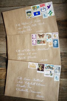 Kraft colored envelopes for the invitations with calligraphy in white ink and vintage stamps.