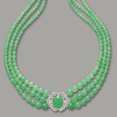 JADEITE AND DIAMOND NECKLACE Set to the front with a translucent jadeite cabochon of apple green colour, to an openwork surround set with circular-cut diamonds, completed by a triple-strand graduated jadeite bead necklace, to a clasp set with jadeite cabochons and circular-cut diamonds, the diamonds together weighing approximately 1.30 carats, mounted in 18 karat white gold,