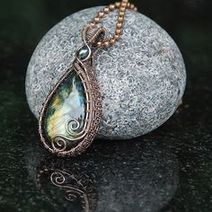 This beautiful labradorite stone has been lovingly wrapped with pure copper wire using a combination of different weaves, shapes and spirals. I try to make the back as attractive as the front so my pendants are reversible.  Photographing Labradorite is notoriously difficult because the light shimmers off at different angles. Ive done my best to show you the beautiful colours in natural daylight. Please also bear in mind that there may be slight differences in the colours and resolution of…