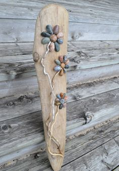 Gorgeous one of a kind beauty piece of Lake Huron driftwood adorned with flowers made from hand gathered beach pebbles and driftwood stick branches. Truly a huge conversation piece. Awesome gift for the gardener or flower lover or just the beach lover on your gift list. This is a rather LARGE piece measuring approx 30 long by almost 9 wide. There is a hook on the back for hanging purposes, it is signed and dated by me and has a had a coat of varnish to seal and protect but NOT recommended…
