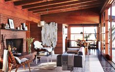 A wood cabin's neutral living space with Hermès blanket and brick fireplace