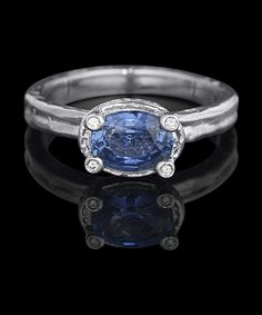 """DESIRE OVAL  The """"Desire"""" ring has a claw setting that incorporates a bezel as a design element, and is feminine but strong.  Shown in hand-textured platinum, this ring is set with a certified 1.27 ct  oval brilliant cornflower blue, natural sapphire and diamonds atop the claws . Looks great with our everlasting or pave' eternity band as a sleek duo.  8,800.00 USD"""
