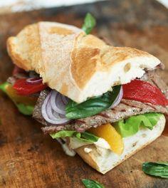 Steak-Sandwich: Zwischem knusprigem Baguette finden wir zarte Rindersteaks, gegrillte Paprika, Salat und einen frischen Joghurt-Dip.