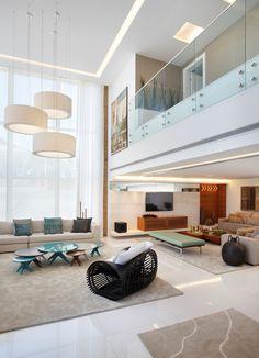 Idéia de modelo de sala, bem aberta, pé direito espaçoso, corredores em cima vistos e divididos por vidro.