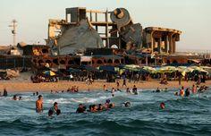 Palästinenser baden im Mittelmeer vor Trümmern: Im Krieg vor einem Jahr wurden...