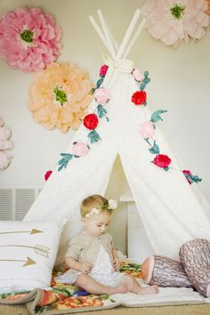 Cute way to dress up Aria's white tent. Love the flower chain and pillow logs!