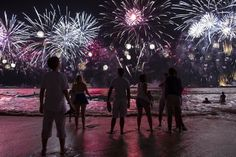 People watch fireworks exploding over Copacabana beach during New Year celebrations in Rio de Janeiro, Brazil, Thursday, Jan. 1, 2015. (AP Photo/Felipe Dana)