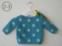 Jersey para bebe hecho a punto bobo con aplicaciones lunares ganchillo. Disponible en color gris plata, verde claro y azul vaquero.