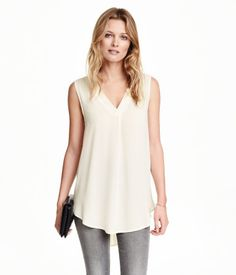 Wide-cut, sleeveless blouse in an airy woven fabric with a satin-trimmed V-neck. Pleat at front, box pleats at back of neck, and a rounded hem. Slightly longer at back.