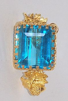 """This exquisite custom handmade pendant is a 110 carat medium dark blue topaz adorned in a heavy 18 carat yellow gold frame of acorns and leaves. It is transparent of the clarity type 1 VVS, with bright brilliance, excellent cut and polish. It is 2 inches long, 1 inch wide and ¾ inch deep. An available 1995 certified gemologist appraisal of  $4,695 makes this a real holiday bargain at $2,650, especially considering today""""s gold values. It is truly a regal piece of jewelry."""