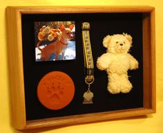 This shadow box is a memorial to Belle, a little Chihuahua who was much loved by her elderly owner. It contains a clay paw print, her favorite toy, her collar and a photo. By ShadowBoxUSA.com.
