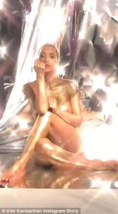 Golden goddess: The entrepreneur showed off her famous hourglass figure, including a hint of her derriere as well her cleavage in the sparkling image; pictured in a behind the scenes clip