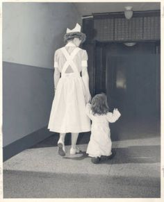 """A young patient 'out for a stroll' with a nurse at the Jewish Hospital of St. Louis, 1950s. """"Bernard Becker Medical Library, Washington University School of Medicine"""""""