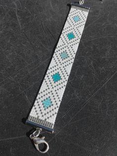 Bracelet tissé avec perles japonaises Miyuki sur un métier à tisser. Couleur : blanc, plaqué argent et 3 bleus différents. Taille du tissage : 13 cm. Largeur : 2 cm. Taille du bracelet : 15,5 cm + 5,5 cm de chaîne dextension. Autres tailles et ou couleurs sur demande. Apprêts en métal argenté sans nickel. Ne pas mouiller et le conserver dans une boîte quand il nest pas porté. ***Merci pour votre visite***