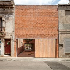 A red brick wall spans the gap between two crumbling facades on a street in Catalonia, hiding a home by H Arquitectes with two courtyards and a central garden.