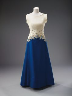 Preview some of the outfits going on display when the exhibition opens at Buckingham Palace on Saturday, 23 July 2016.Evening Dress, Norman Hartnell, 1967TheQueen wore this dress during a visit to Ottawa to mark the centennial celebrations of the Confederation of Canada.The embroidery design was a fitting compliment to the Canadian people on this historic occasion. An inverted v-shaped panel of rich embroidery in the form of maple leaves descends from the waist, over…