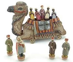 papier-mâché and wood camel on wheels pull toy and nodder houses a skittles set of figural ninepins.