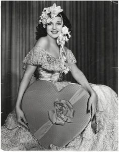 Rita Hayworth looking as sweet as the over-sized box of chocolates she's holding.1940's