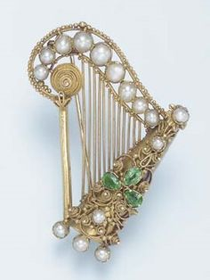 AN ANTIQUE EMERALD, PEARL AND GOLD BROOCH. Designed as a gold harp, with gold…