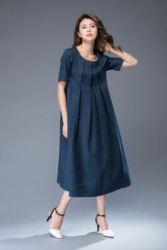 This loose-fitted summer dress has a romantic and slightly vintage vibe. Wear your hair in loose waves, add chunky jewelry and gladiator sandals for a more boho style. Equally, this dress would look great with court shoes, a clutch handbag and a chunky belt for wearing to the office. This is a very versatile dress than can be dressed up or down.  The navy blue linen dress has some gorgeous big pleats on the bodice that run all the way down the front. It also has short sleeves, a round neck…