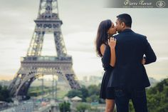 Engagement picture with a kiss in front of the Eiffel Tower