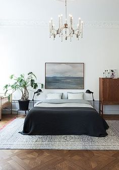 Mid-century modern furnishings and a controlled minimalist color palette get a majorly glam upgrade with a nautical oil painting and vintage bronze chandelier.