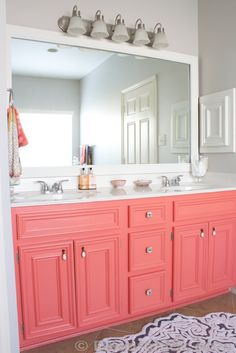 Gorgeous coral color painted bathroom vanity cabinet. Love the pop of color against the neutral grey walls. Inspiring DIY makeover from Decorchick.