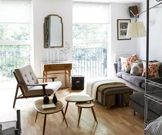 """A small living room made to look more roomy by using """"leggy"""" furniture that maximizes the flow of air and light from the windows. Expert Advice: 11 Tips for Making a Room Look Bigger @Remodelista"""