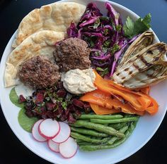 A Mediterranean feast for the eyes! 👀 Kontos Pita is the backdrop to this pretty spread: Mini kofta patties with hummus, grilled endive, roasted red bell peppers, steamed green beans, radishes, greens and homemade tahini sauce from @isolatedplate. 😍