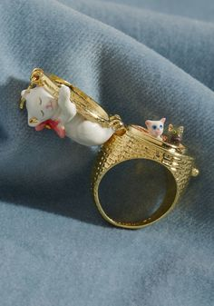 Les Nereides Little Cat Ring - Sometimes, there's nothing sweeter than a bit of girlish glam - and French brand Les Nereides knows exactly how to deliver. Made from delicate, 14k gold and hand-enameled brass, this statement ring touts a sleeping mother cat with two kittens secretly hidden in the basket upon which she lounges. Trop mignon!