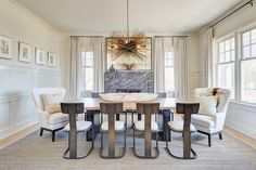 source: Tamara Magel  Holiday House Hamptons 2013 - Fabulous dining room features mirror over black marble fireplace flanked by wind...