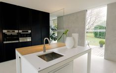 modern minimalist kitchen with hybrid island table worktop and industrial sink