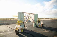 ceremony setup - photo by Sarah Tamagni Photography http://ruffledblog.com/stormy-day-plane-hangar-wedding