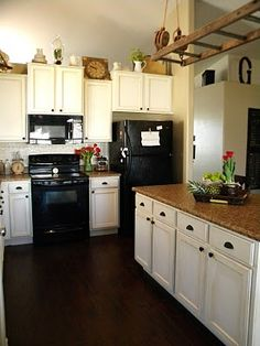 White cabinets with black appliances - white tin backsplash, dark wood floor, mid range brown counter. - would tie into the rest of the black/brown/green house.