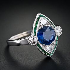 Art Deco original antique ring. Round 1.4ct sapphire in navette-shaped silhouette bordered by emeralds and  European cut diamonds. 14K white gold setting.