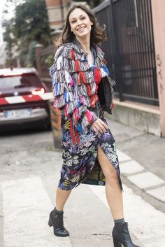 A colorful fringed jacket and rainbow patterned skirt.