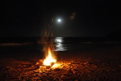 Noite de lua com fogueira na praia