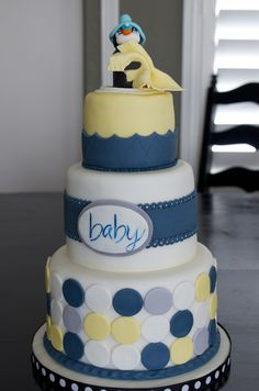 "Baby shower cake....nursery colors are navy blue, yellow, gray and white. Mom to be loves penguins so there is a baby penguin on the top. 8"", 6"" and 4"" tiers covered in marshmallow fondant."