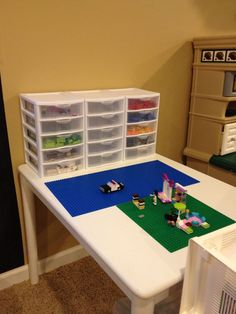"""Lego table made from a $10 garage sale kid sized table & chairs.  Sterlite storage bins(from amazon) I planned to hot glue the blue lego plates to the table but I think I will find another way to attach them so we can still use this table for other purposes(it use to be the""""craft table"""")"""