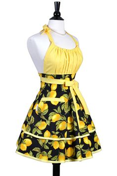 A flirty retro pinup kitchen apron in farmers market yellow lemons on black with full skirts. Bodice has elastic at top for comfortable fit on women of all bust sizes. Dress this apron up with heels or down with jeans, either way you cant go wrong! Details: - 100% Premium Cotton;