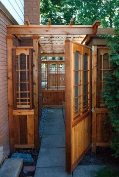 A stunning privacy gate in red cedar with similar open side screens and integral pergola headpiece.