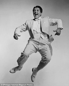 Pianist Liberace can be seen jovially jumping wearing a white tuxedo in 1954.....Uploaded By www.1stand2ndtimearound.etsy.com