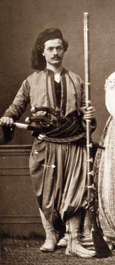 """Christian horseman of Hanı̈a (Chania), Ottoman Crete, holding a flintlock rifle and wearing a weapons belt (silahlik) containing a yatagan and two pistols (kuber). From:Les costumes populaires de la Turquie en 1873, 74 photographic plates by Pascal Sebah, published by the Imperial Ottoman Commission for the """"Exposition Universelle"""" of Vienna in 1873."""