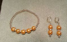 Gold tone pearls with rhinestones and metallic gold beads stretch bracelet, dangle earrings with lever back wires